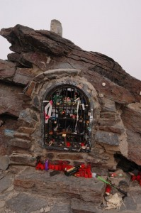 shrine at Mulhacen summit, with candles, broken walking poles, and brandy